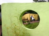 Curved, rendered walls separate the gardens