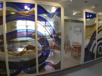 A stained glass wall divides the day room from the ward